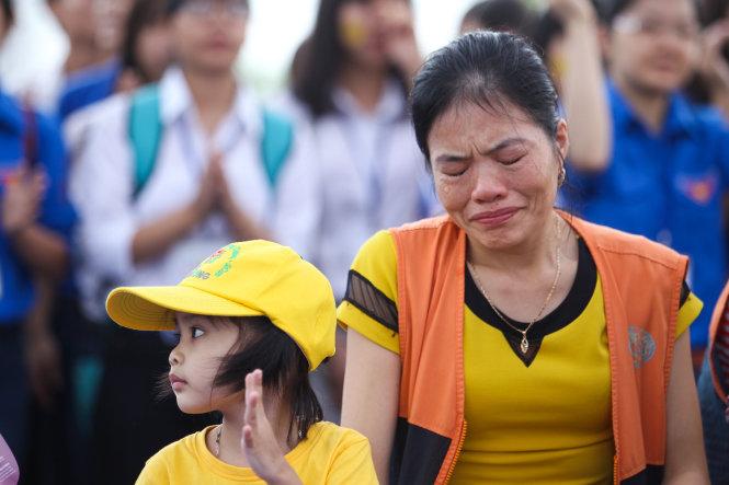 Chị Lê Thị Xuân bật khóc khi xem một tiết mục văn nghệ của các bệnh nhi tại ngày hội ở Hà Nội. Chị Xuân (quê Thanh Hoá) đưa con gái Trần Thị Tuyết Nhi 4 tuổi bị ung thư máu (trái) lên Viện huyết học truyền máu TƯ điều trị - Ảnh: Nguyễn Khánh