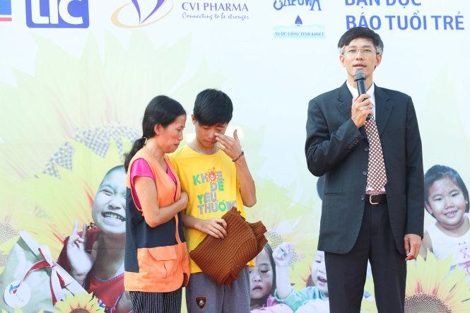 Đại diện của công ty dược phẩm ECO dành tặng 5 triệu đồng và một chiếc áo cho hai mẹ con bệnh nhi Nguyễn Văn Truyền - Ảnh: Nguyễn Khánh