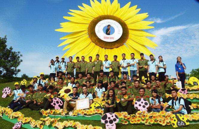 Chụp hình lưu niệm bên đóa hoa hướng dương khổng lồ - Ảnh: Ngọc Hiển